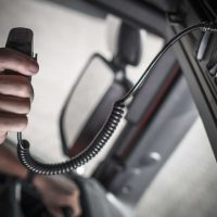 CB Radio Talk While on the Road. Truck Driver Using Radio To Contact Other Convoy Drivers.